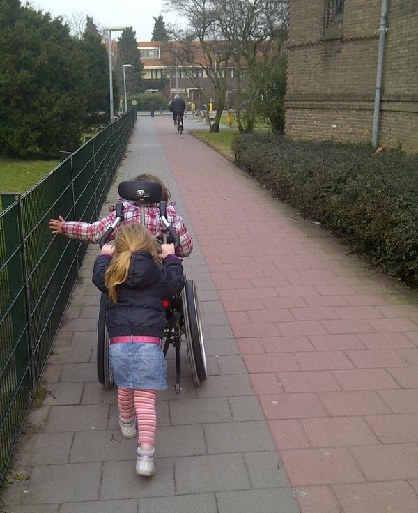 Zus duwt rolstoel van zus