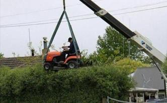Met een grasmaaier de bovenkant van de heg maaien of snoeien